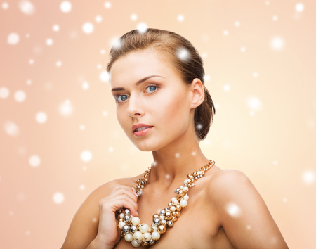 jewel hands: beauty and jewelery concept - beautiful woman wearing statement necklace with pearls