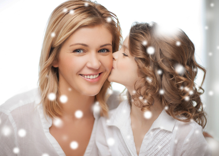 family, children, christmas, x-mas, love concept - happy daughter kisses her mother photo