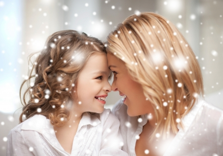 family, children, christmas, x-mas, love concept - mother and daughter cuddling photo