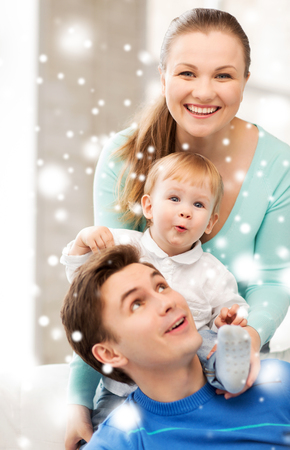 family, children, christmas, x-mas, love concept - happy parents playing with adorable baby photo