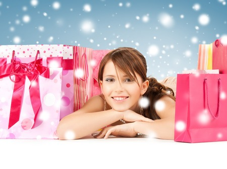 sale, christmas, x-mas and holidays concept - happy girl with shopping or gift bags photo