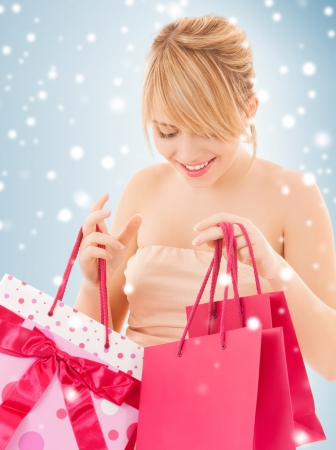 sale, christmas, x-mas and holidays concept - happy teenage girl with many shopping bags photo