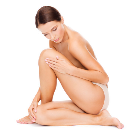 nude girl sitting: health and beauty concept - beautiful naked woman touching her legs