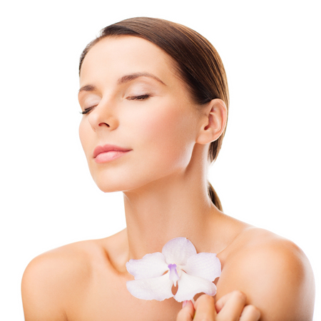 health and beauty concept - relaxed woman with orhid flower photo
