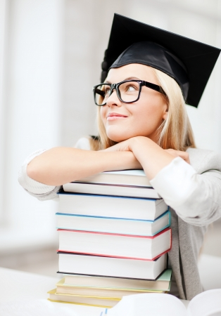 business and education concept - happy student in graduation cap with stack of books photo