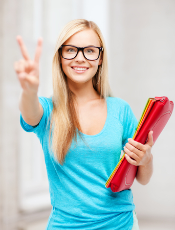 education and school concept - smiling student with folders showing victory or peace sign photo