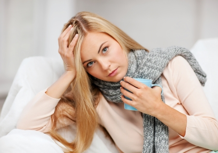 cold sore: health and illness concept - indoor picture of diseased woman with cup of tea