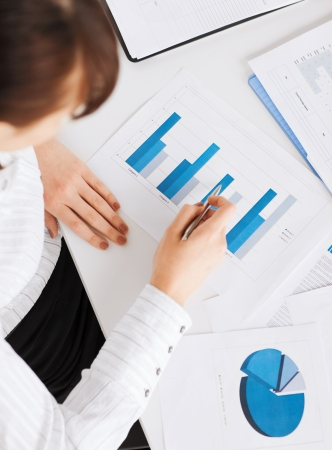the bookkeeper: business, office, school and education concept - woman hand with charts and papers