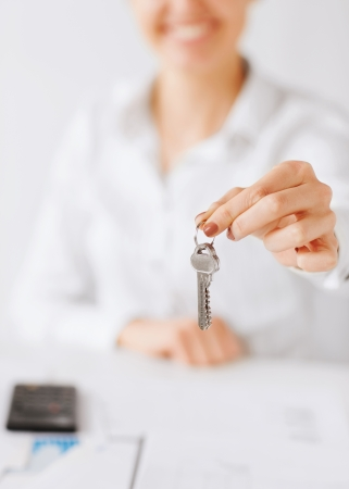 business, banking, real estate concept - woman hand holding house keys Stock Photo - 22381540
