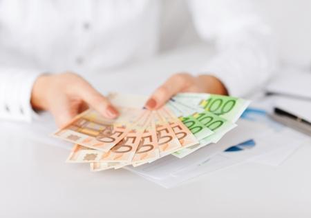 zaken, bureau, huishouden, bankieren, belastingen, gokken concept - vrouw handen met euro contant geld