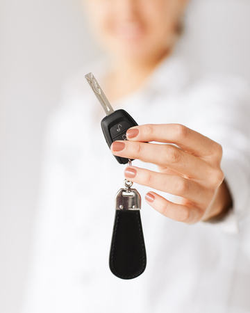 business, banking, vehicle, rental, automotive concept - woman hand holding car key photo