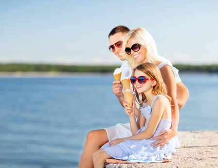 summer holidays, celebration, children and people concept - happy family eating ice cream photo