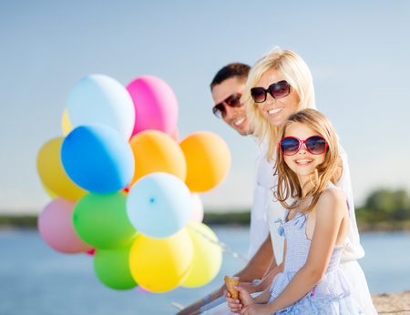 summer holidays, celebration, children and people concept - family with colorful balloons photo