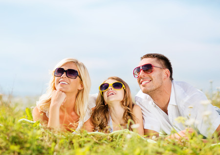 summer holidays, children and people concept - happy family with blue sky and green grass photo
