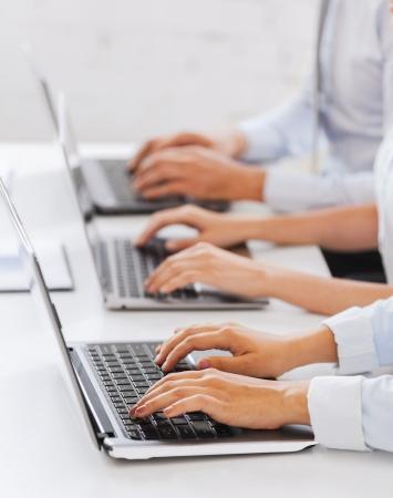 entreprise, l'école et le concept de l'éducation - un groupe de personnes qui travaillent avec les ordinateurs portables dans le bureau