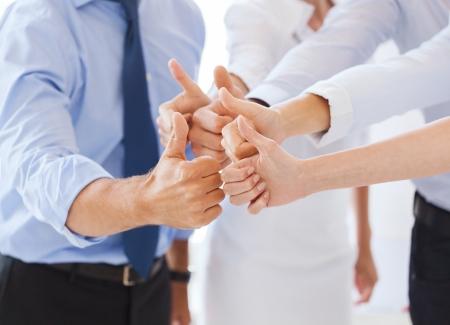 幸せなビジネスのチーム表示のオフィスで親指を成功と勝利の概念-