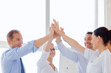team victory: success and winning concept - happy business team giving high five in office