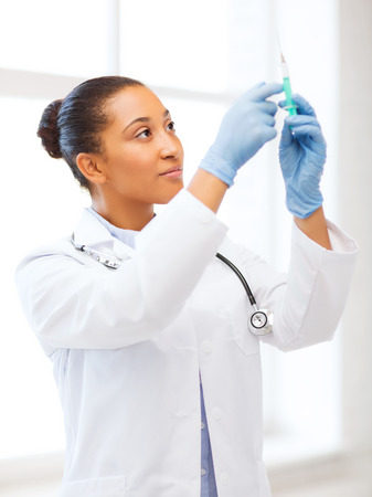 injection woman: healthcare and medical concept - african doctor holding syringe with injection