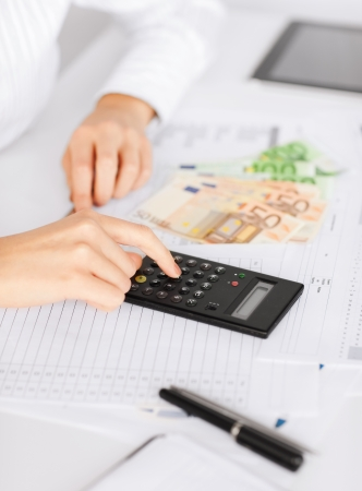 household money: business, office, household, school, tax and education concept - woman hand with calculator and euro money