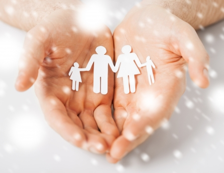 love, romance, safety concept - man hands showing family of paper people photo