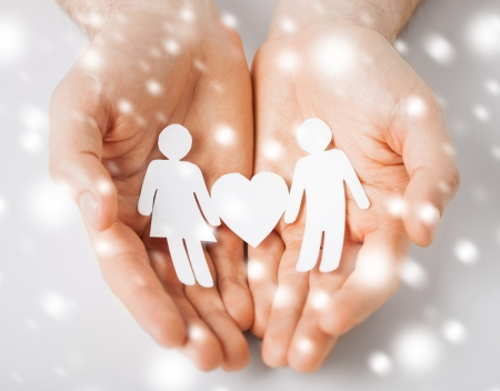 love, romance, safety concept - man hands showing two paper people with heart shape photo