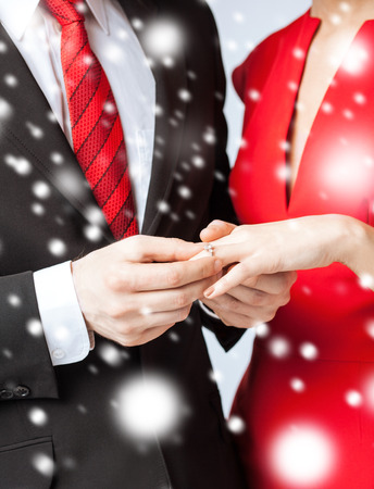 putting on: love, romance, marriage, jewelry concept - man putting wedding ring on woman hand Stock Photo