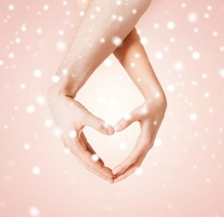 forme: harmonie, l'amour, la famille et le concept de charité - femme et homme mains montrant forme de coeur Banque d'images