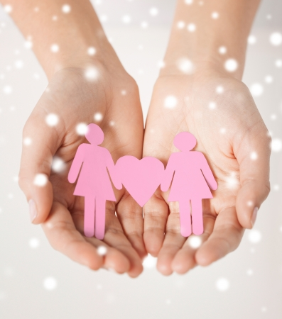 love, romance, human rights, lesbian, family concept - woman hands showing two paper women with heart shape photo