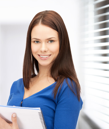 buisness woman: office, buisness, education concept - happy woman with big notepad