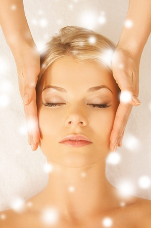 health and beauty concept - woman in spa salon getting face treatment photo