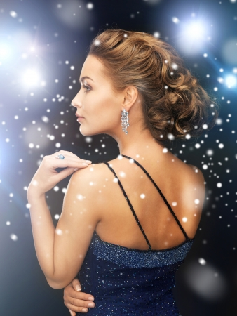 jewelry, luxury, vip, nightlife, party concept - beautiful woman in evening dress wearing diamond earrings photo