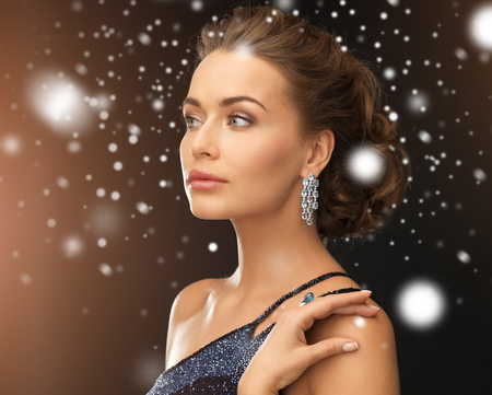 jewelry, luxury, vip, nightlife, party concept - beautiful woman in evening dress wearing diamond earrings Stock Photo - 22641740