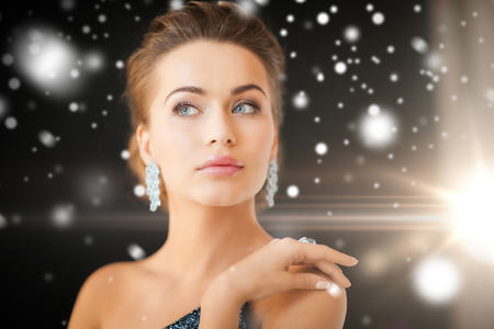 jewelry, luxury, vip, nightlife, party concept - beautiful woman in evening dress wearing diamond earrings Stock Photo - 22641762