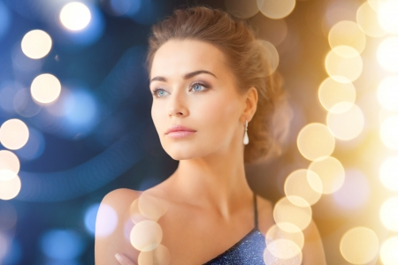 jewelry, luxury, vip, nightlife, party concept - beautiful woman in evening dress wearing diamond earrings Stock Photo - 22641767