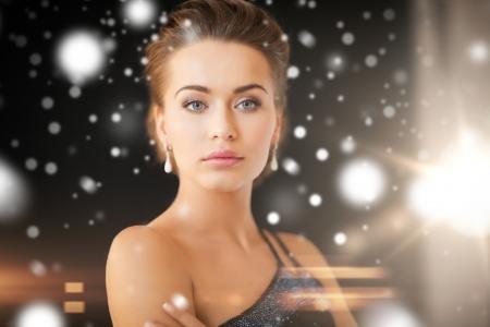 jewelry, luxury, vip, nightlife, party concept - beautiful woman in evening dress wearing diamond earrings Stock Photo - 22641769