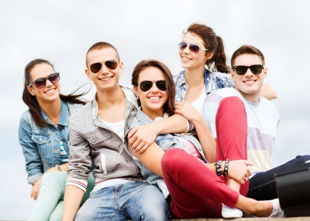 mates: summer holidays and teenage concept - group of teenagers hanging outside Stock Photo