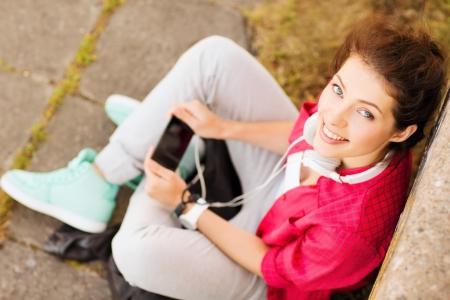 youngsters: summer holidays and teenage concept - teenage girl with headphones listening to music outside Stock Photo