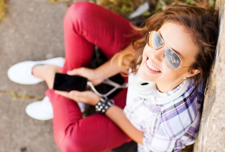chilling: summer holidays and teenage concept - teenage girl with headphones listening to music outside Stock Photo
