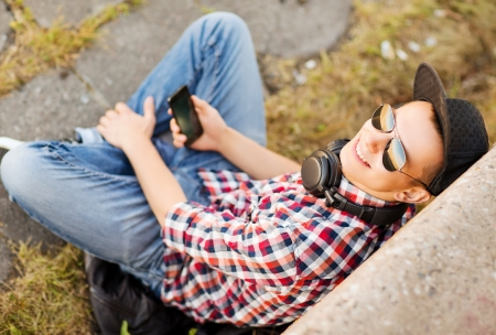 summer holidays, teenage and technology concept - teenager with headphones and smartphone outside photo