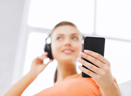 home, music, internet and shopping - woman with headphones and smartphone at home photo