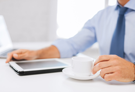 business, office, school and education concept - businessman with tablet pc drinking coffee in office photo