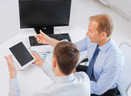 businesss and office concept - businessmen with notebook and tablet pc discussing graphs on meeting photo