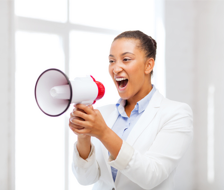 business and communication, bad boss concept - strict businesswoman shouting in megaphone in office photo