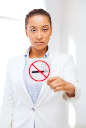 black girl smoking: health and healthcare concept - picture of african woman with restriction no smoking sign Stock Photo