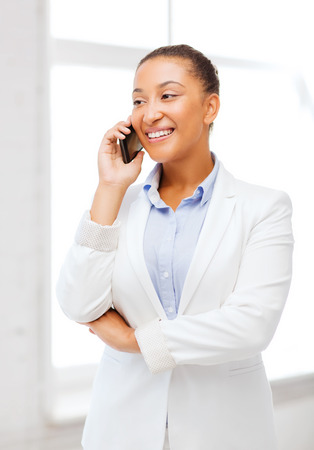business, and communication concept - smiling african businesswoman with smartphone in office photo