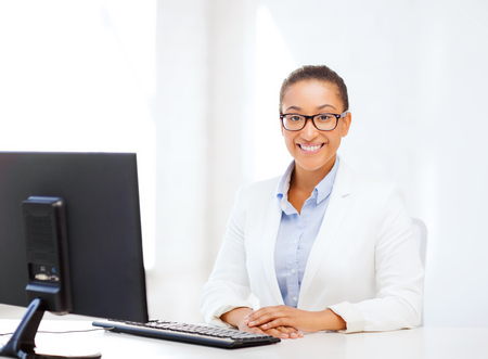 african business woman: business and internet concept - smiling african businesswoman with computer in office