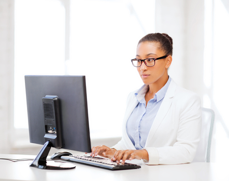 business and internet concept - african businesswoman with computer in office photo