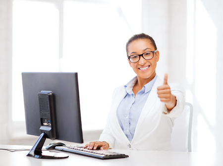 business and internet concept - smiling african businesswoman with computer in office showing thumbs up photo