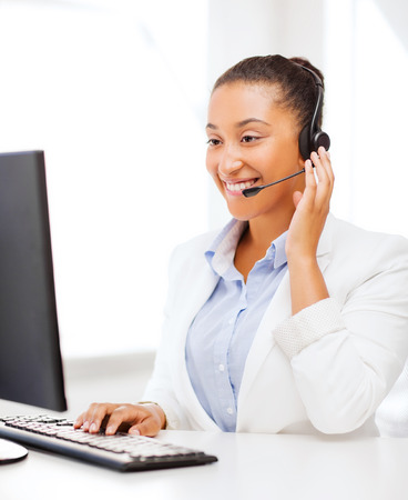 call center agent: business, office and communication concept - african female helpline operator with headphones