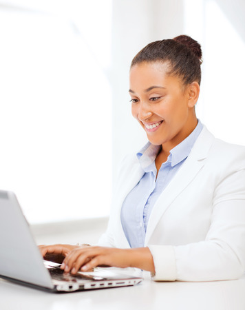 business and technology concept - african businesswoman with laptop in office photo